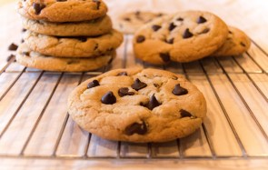 Chewy dark chocolate chip cookies, with a closeup focus and blurred background in natural light.