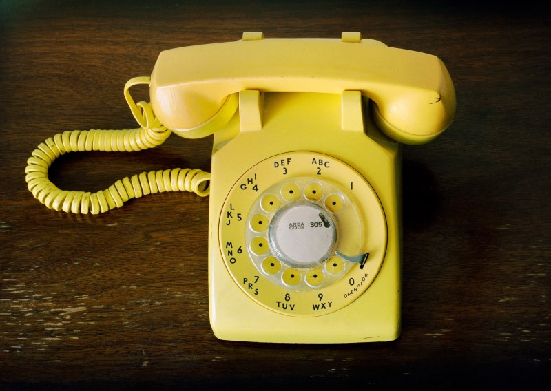 """""""This is a horizontal photograph of a bright yellow rotary phone. The perspective is overhead, looking down. The vintage telephone sits on top of a wood surface."""""""