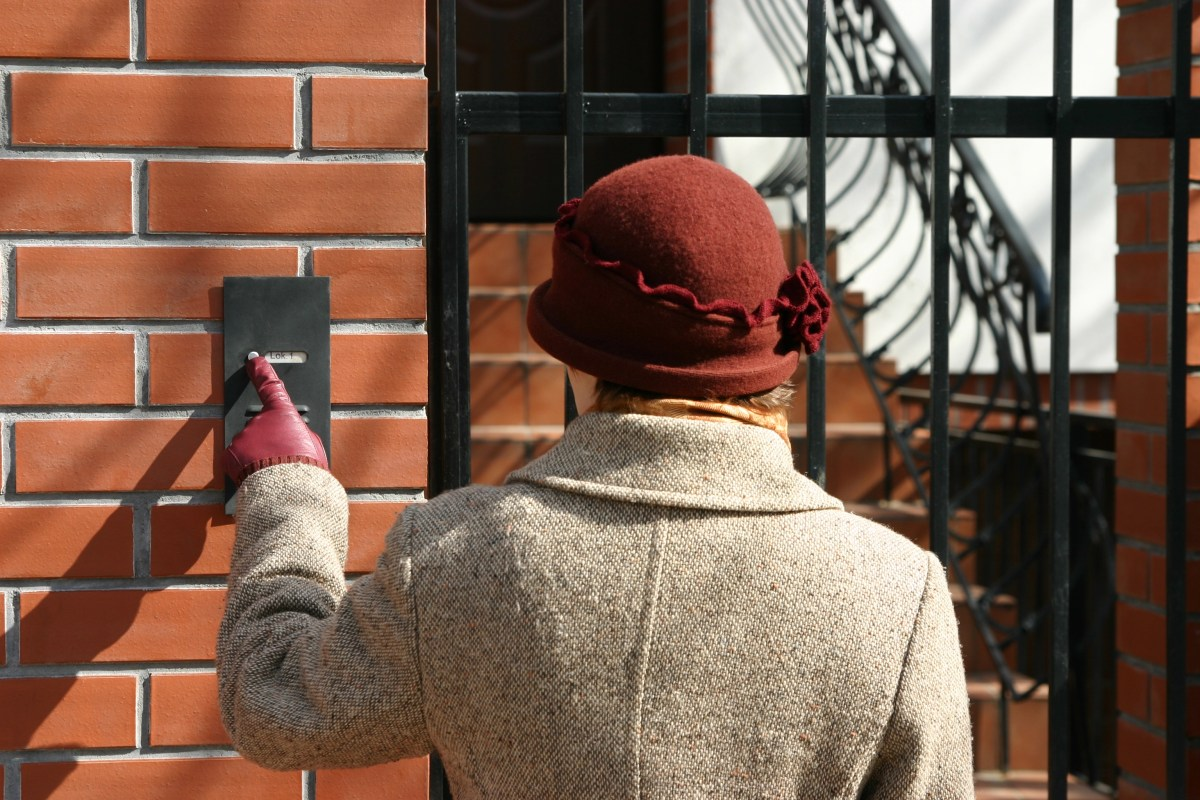 Woman ringing a doorbell.
