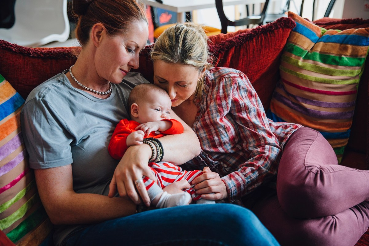 Same sex couple enjoying a cuddle with their baby daughter on the sofa.