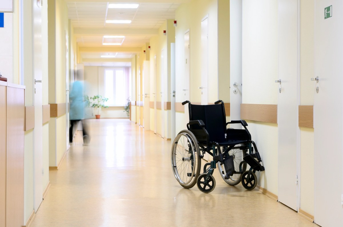 Wheel chair at the hospital corridor. Black wheel chair at the corridor of hospital.