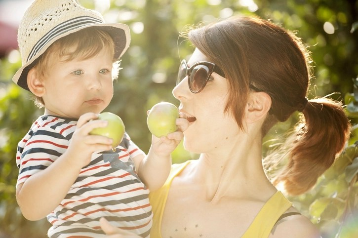 Young Mother and her Son Picking Apple