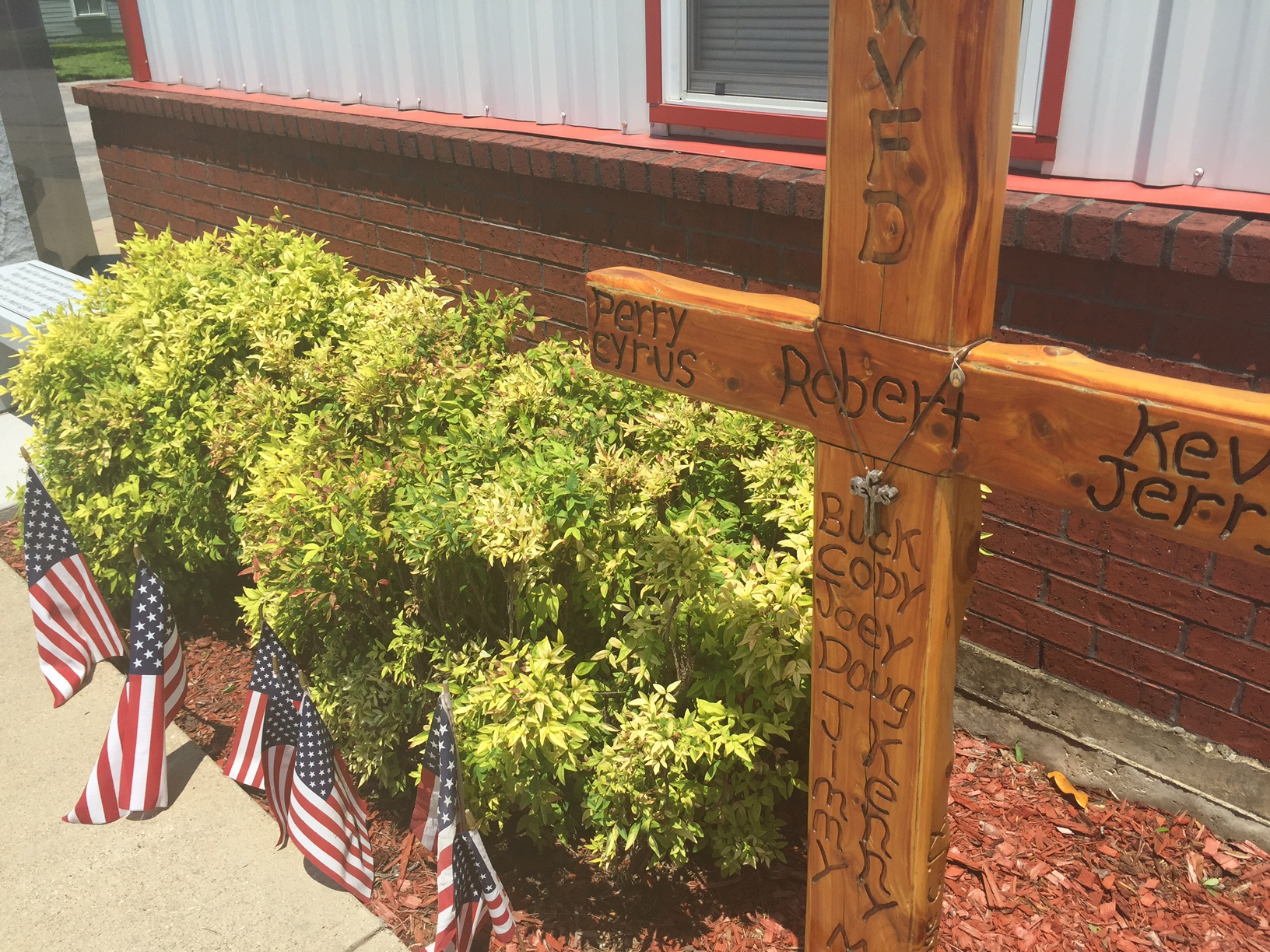 Small flags adorn the base of wooden cross outside the West VFD, May 2016. The marker bears the names of the first responders who died in the W_283870
