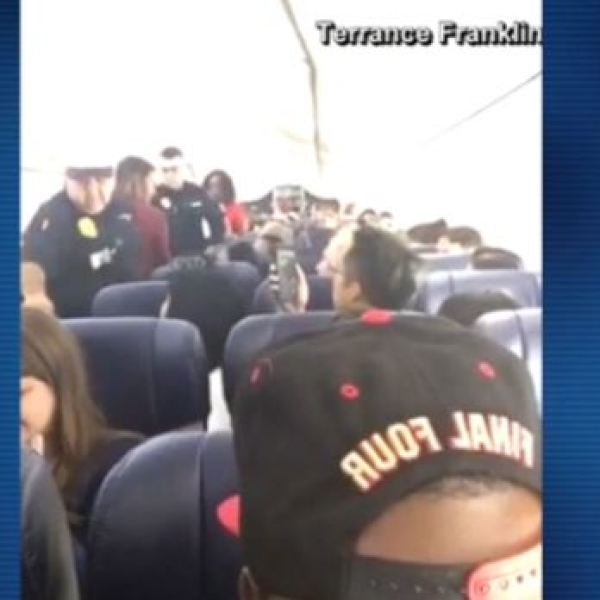 Police escort a disruptive passenger on a flight to Houston off the plane, after making an emergency landing in Corpus Christi_496039