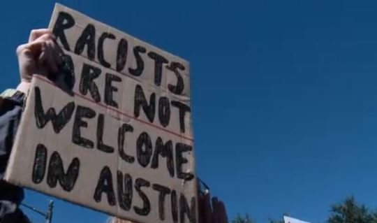 A protester holds a sign outside the Texas Capitol that says _racists are not welcome in Austin.__525821