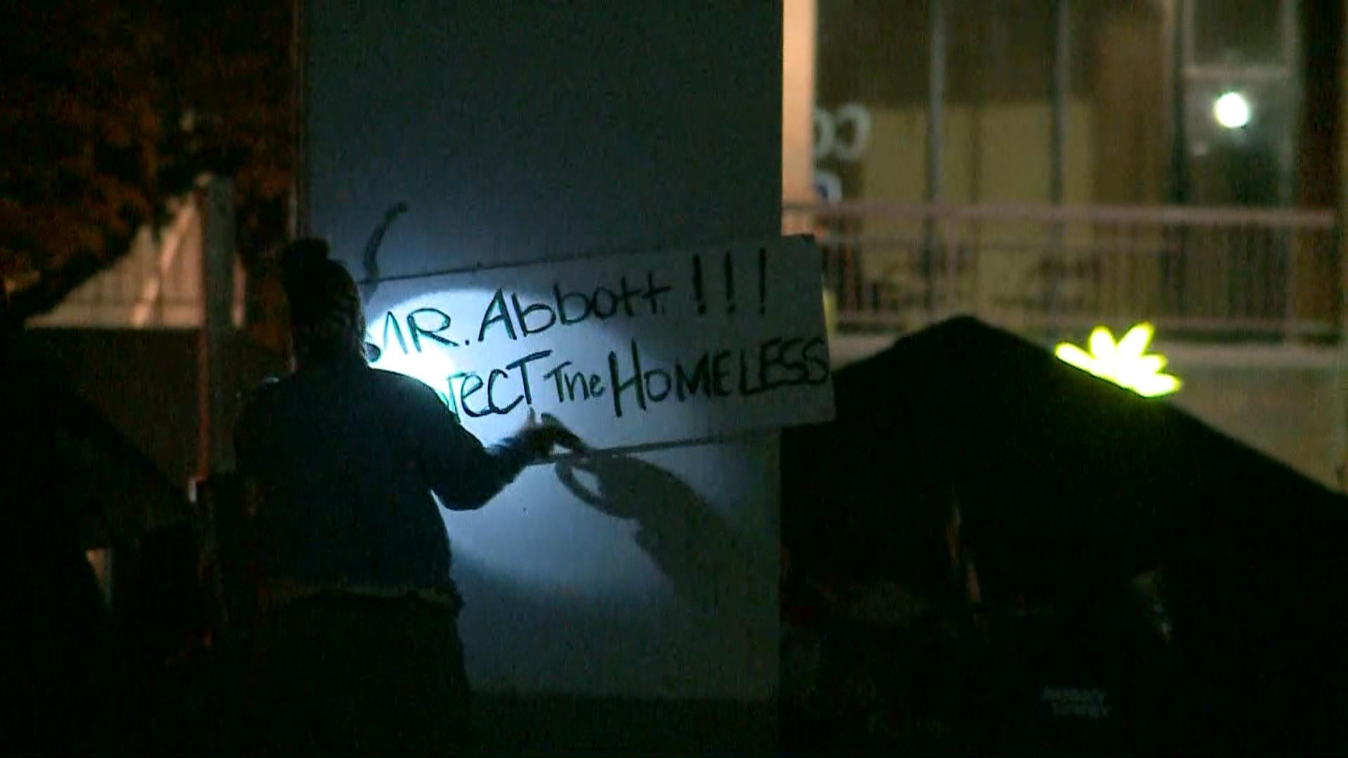 "A homeless woman affixes a sign to a column underneath an overpass that reads ""Mr. Abbott Protect the Homeless."""