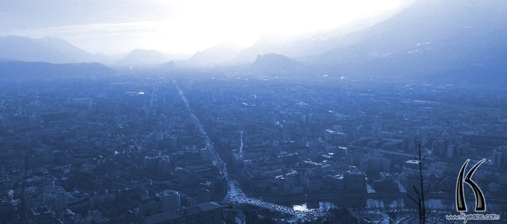 Distant long perspective on town of Grenoble, France, in blue atmosphere by Kyesos