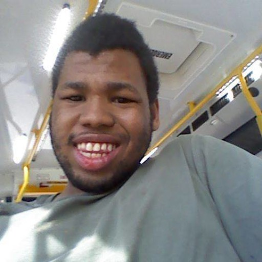 Kylie Brooks, a Black darkskinned person, is pictured in a paratransit vehicle,. She is smiling.