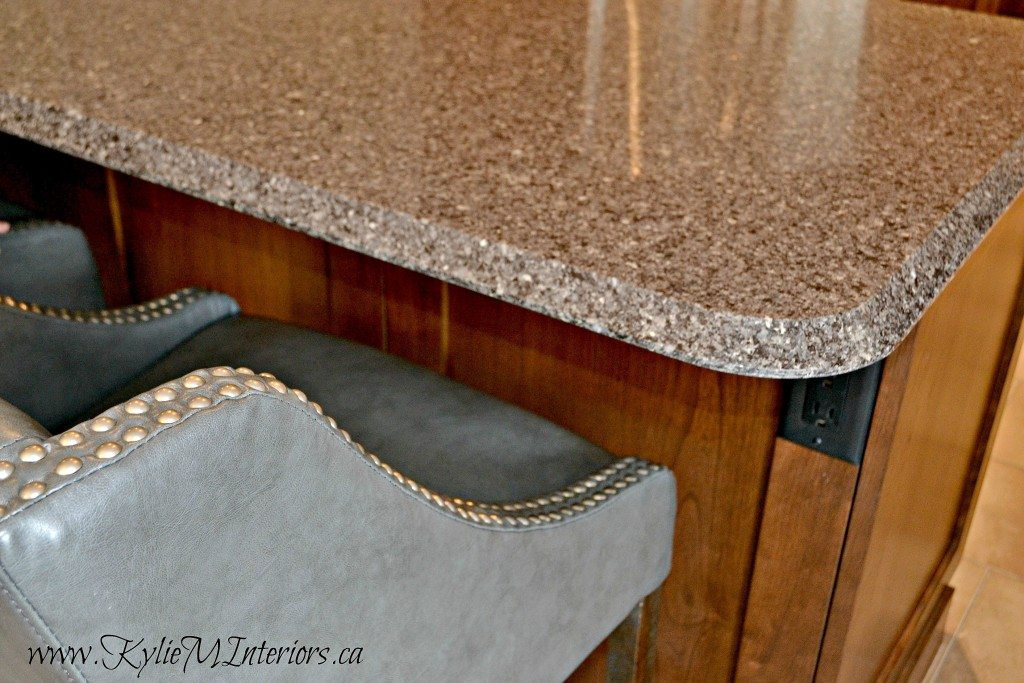 Speckled Quartz countertop wood cabinets and gray leather