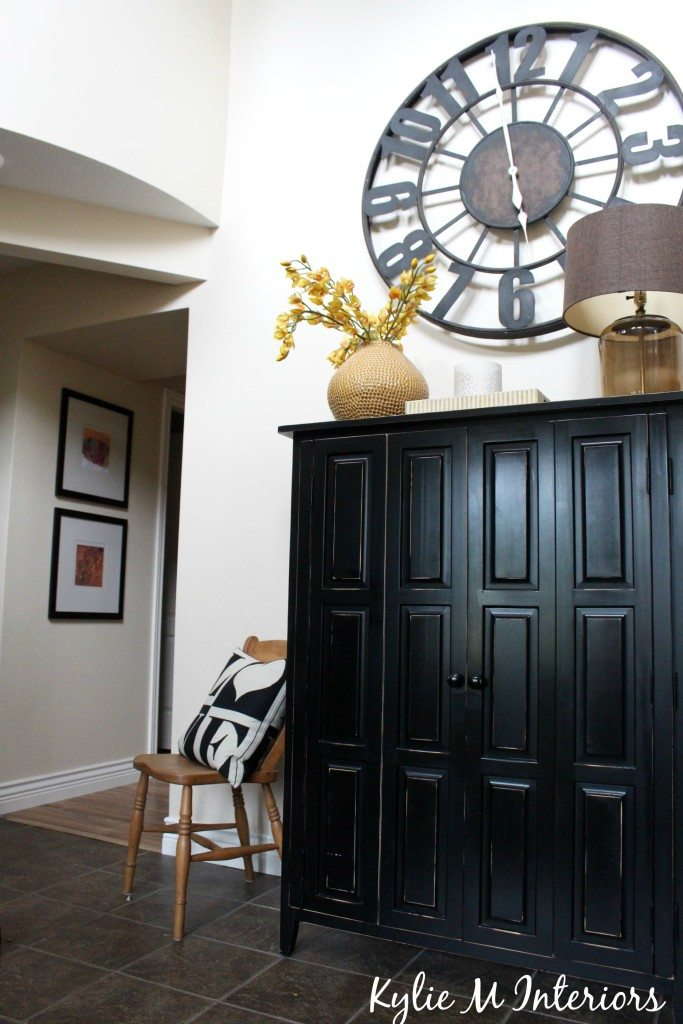 entryway and hallway door removed with large clock black armoire and artwork