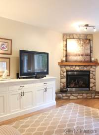 living room with corner stone fireplace. Tv stand that