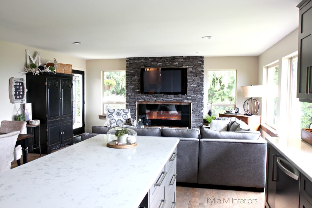 Great room with open layout ledgestone fireplace with TV above and reclaimed wood White quartz