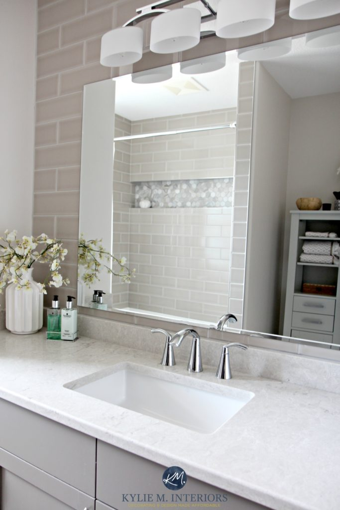 Bathroom with subway tile wall behind vanity Bianco Drift quartz by Caesarstone and Moen Glyde