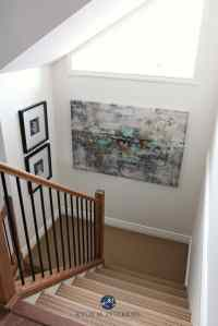 Stairwell with beige carpet, wood and metal railing and ...