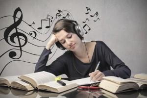 woman writing while using headphone