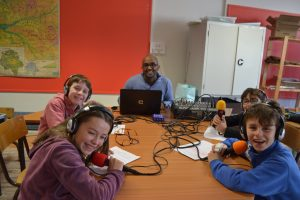 Quatre élèves de CM1 sont installés devant les micros avec les casques sur la tête afin d'entendre leur voix