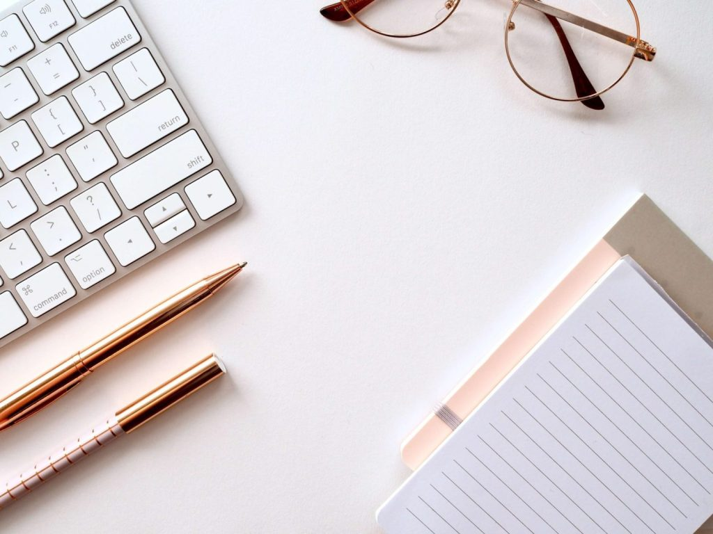 a desk with reading glasses, a laptop keyboard, peach colors
