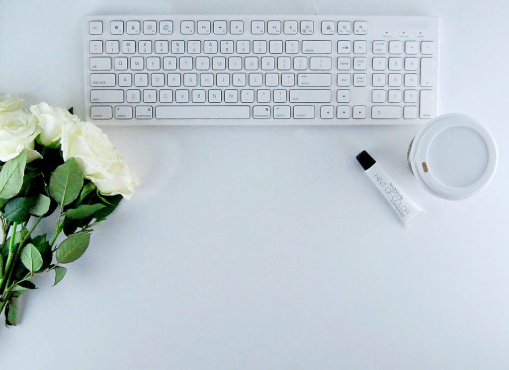 a laptopo with a bouquet of white flowers