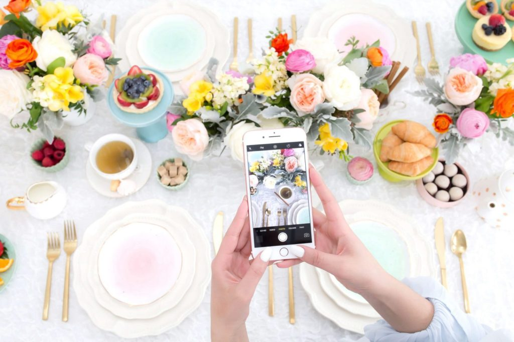 a phone taking a picture from a table that is filled with colorful flowers, from above