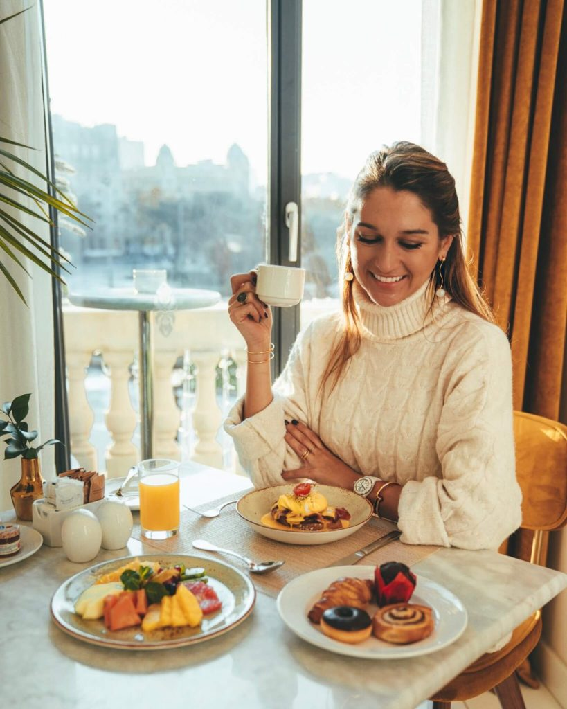 Girl having breakfast and drinking coffee at a hotel in Barcelona Spain