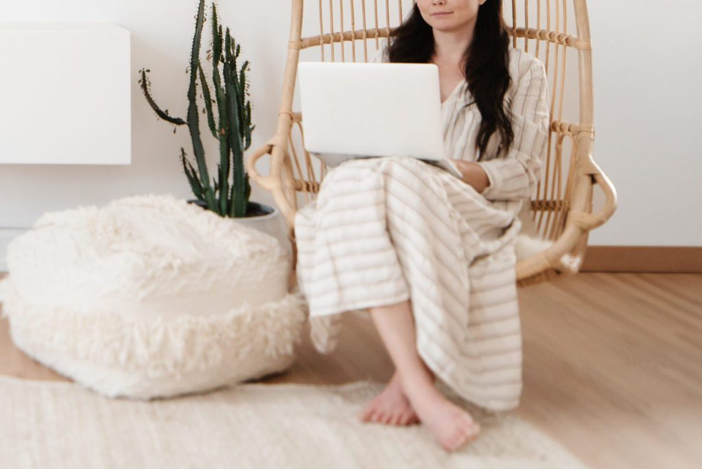 Girl sitting in a minimalist living room with her laptop on her lap