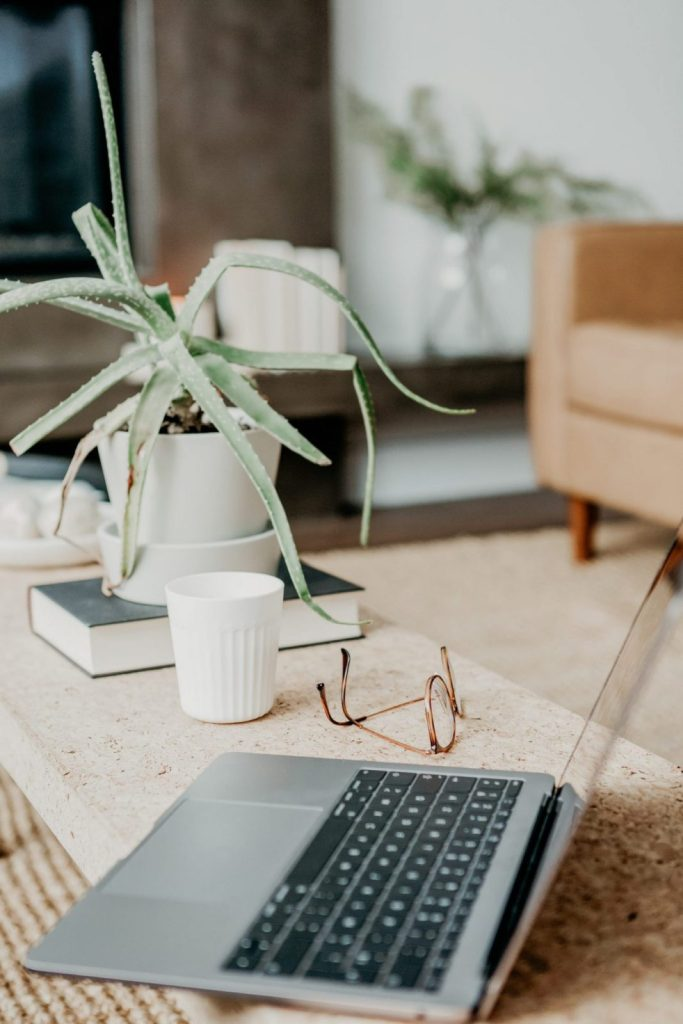 a laptop on top of a coffee table tip reading glasses by its side