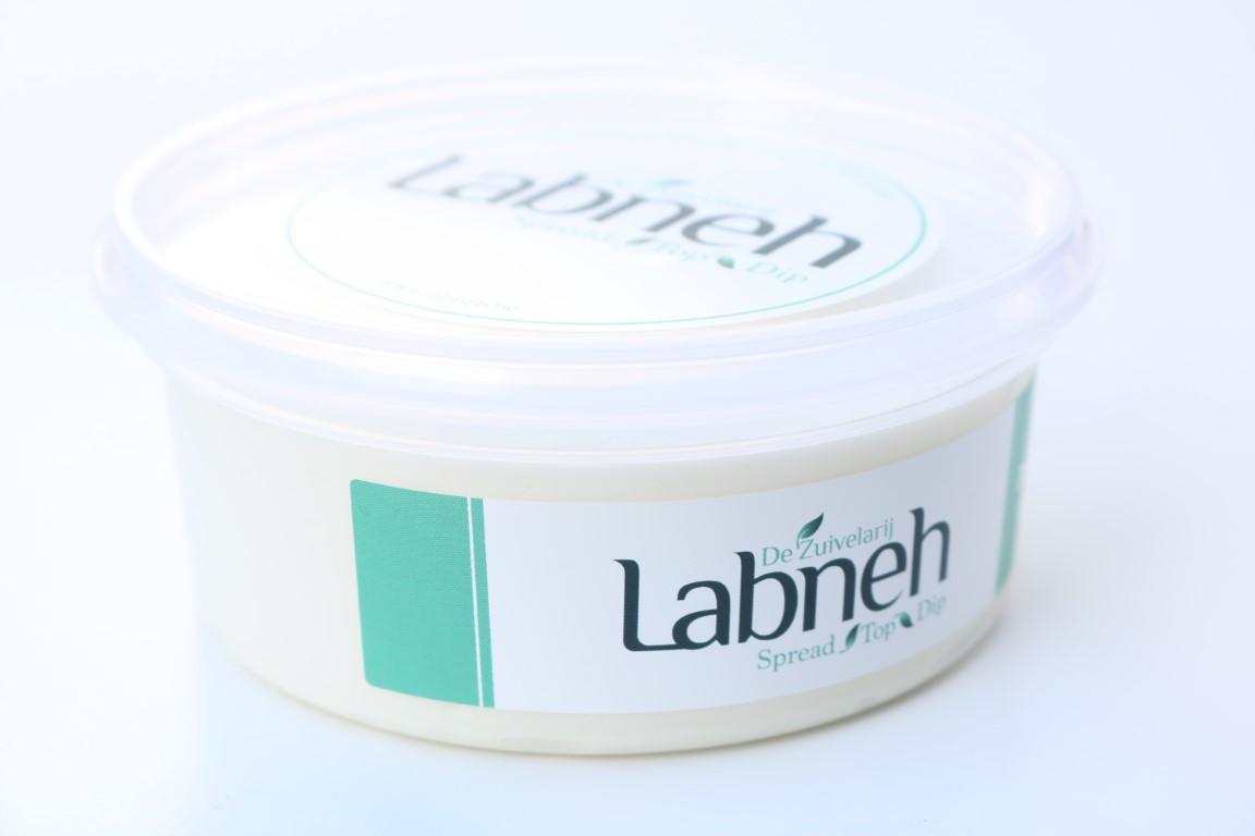 Labneh, ingedikte yoghurt in elegante verpakking op witte achtergrond.