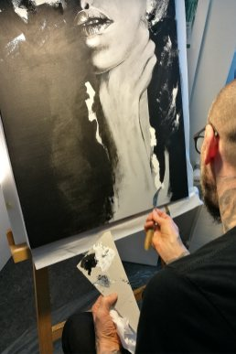 "Guy working on his artwork ""W(hu)man Suffering"""