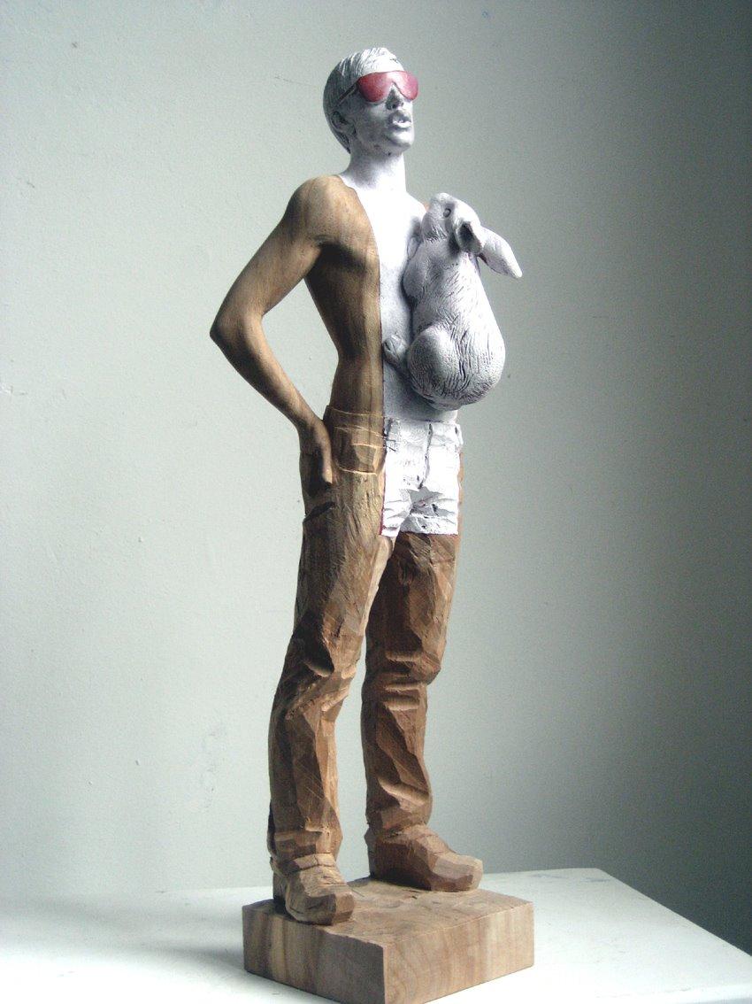Des sculptures en bois de personnages partiellement recouverts de peinture