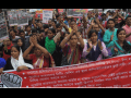 Bangladeshi workers rally behind a banner
