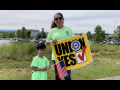 """Woman holding """"UNION YES"""" sign and child holding U.S. flag, with VW plant behind"""