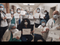 """Masked health care workers in a hospital hold signs reading: """"We... are... here... at... work... for.. you... Please... stay... home... for us."""""""