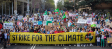 """huge crowd of people, front row carries """"global strike for the climate"""" banner"""