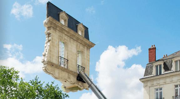 Una casa suspendida de una escalera y un avión en la pared 2