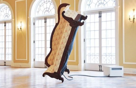 Un sofá que mantiene el equilibrio sobre una pata
