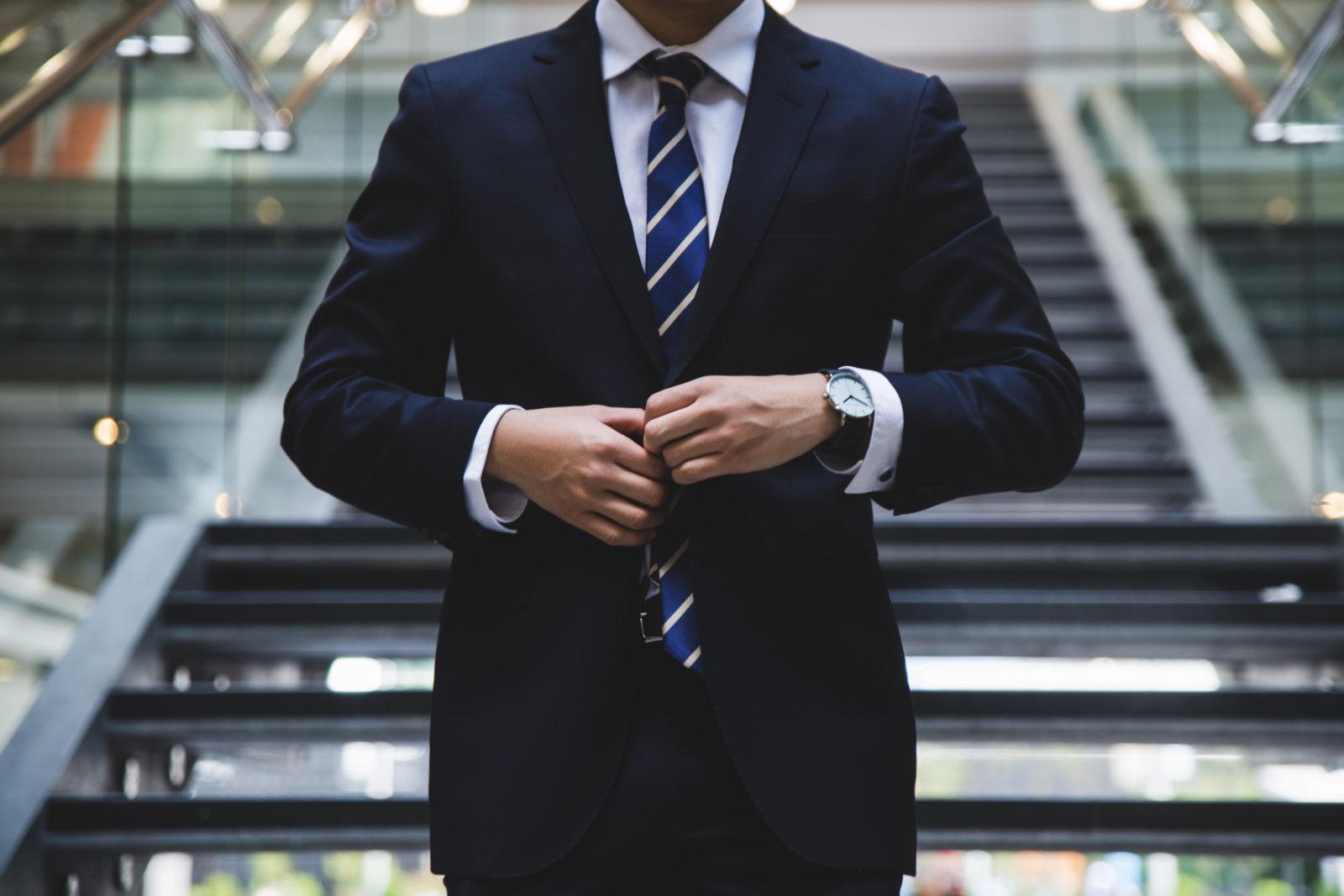 Ein Mann steht, das Gesicht dabei ist nicht erkennbar und knöpft sich das Jackett zu