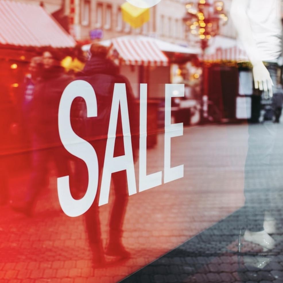 Glasfassade eines Geschäftes mit rotem Sale Schild