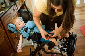 Melanie straps her son Russell into his chair. The 2-year-old suffers from the inherited disease Tay-Sachs, which typically results in death by the age of four.