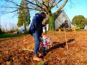 Yaelle et Christophe plantent un pommier. On aperçoit en arrière-plan les licornes du voisin. Elles se sont offertes une petite visite à la ferme.