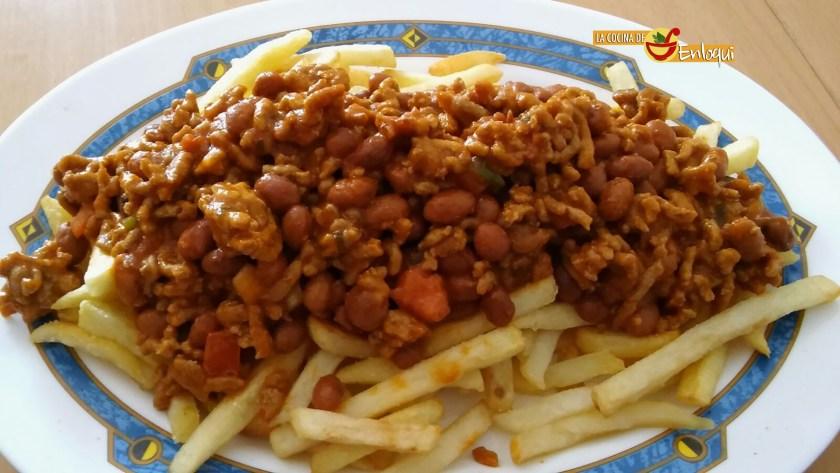 Carne con frijoles sobre patatas fritas