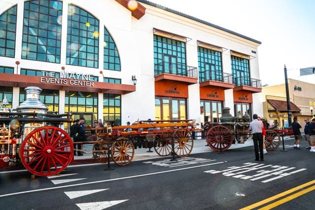 Outside shot of the Museum with 1800s wagons and steamers in the front on Bellflower Boulevard