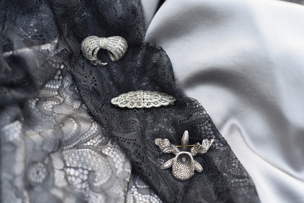 Marcasite brooches on silk and lace