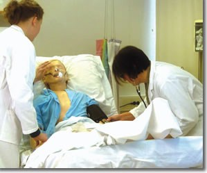 Two Gjøvik University College student examining a simulated patient.