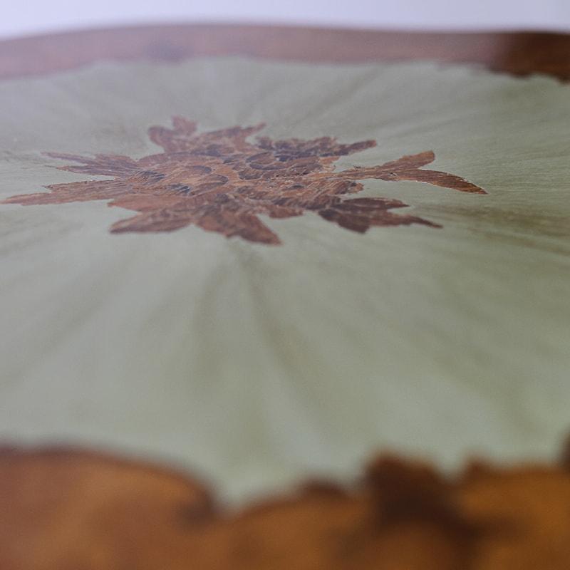 Détail d'une marqueterie sur une table guéridon relookée par La Fée Caséine