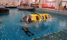 Ihmiset sisällä on kiinnitetty turvavöihin, jotka avataan veden alla ja poistutaan ikkunoista