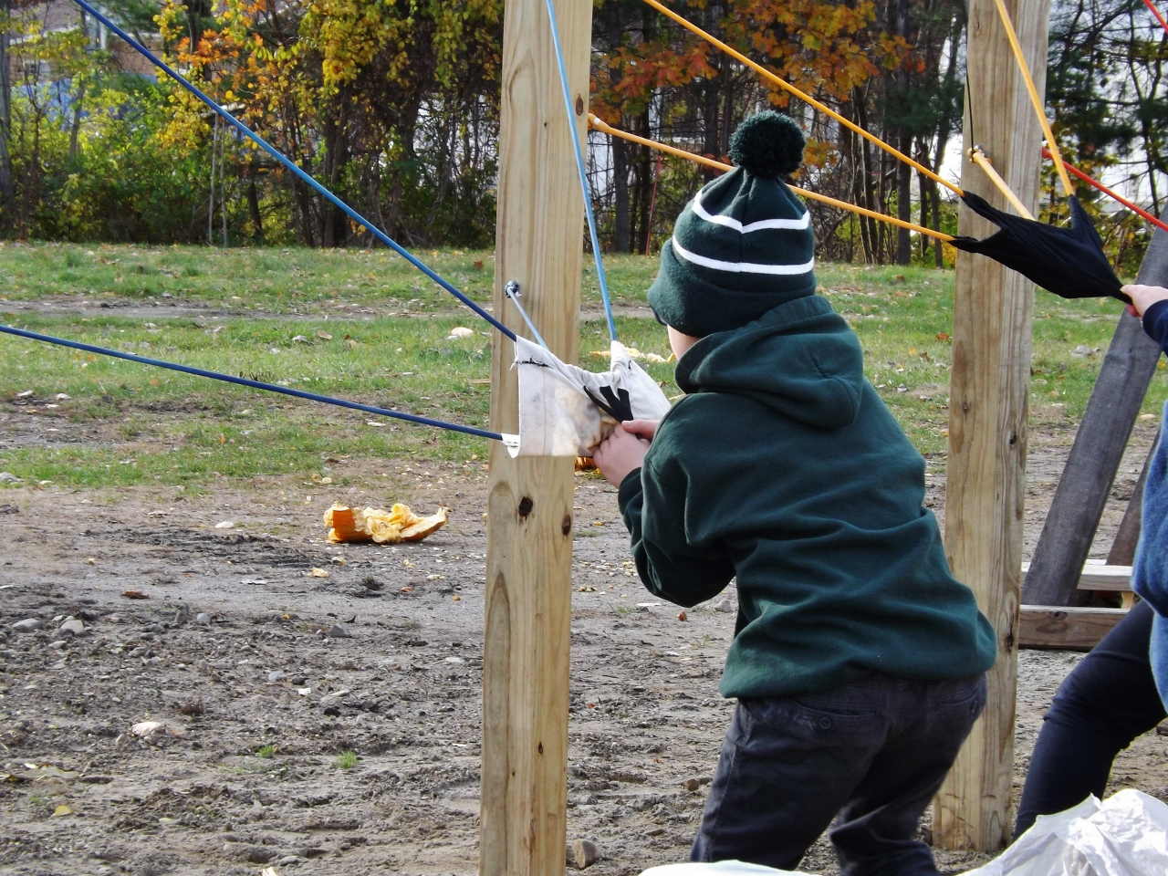 A boy aims with an apple slingshot.