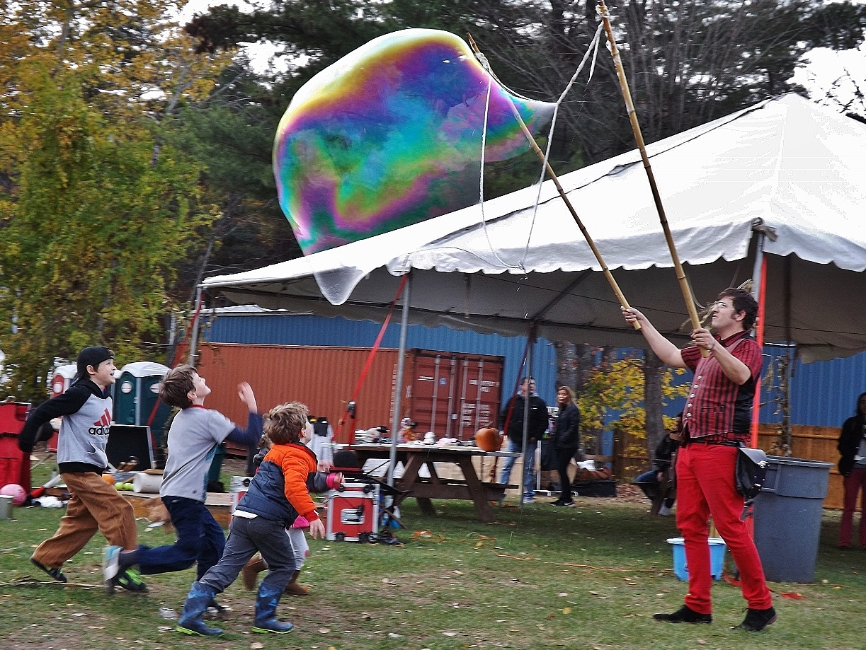 Children chase large bubbles created by Douglas Stafford of Bad Idea Entertainment.