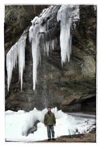 Man standing below Frozen Bridal Veil Falls, North Carolina waterfall, in Highlands