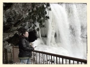 Dry Falls, North Carolina waterfall, forms an ice cave with man standing in front, on the Gorge Road, Highlands