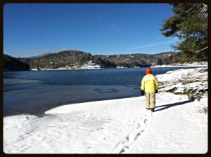 Man walking in snow next to Lake Glenville, NC